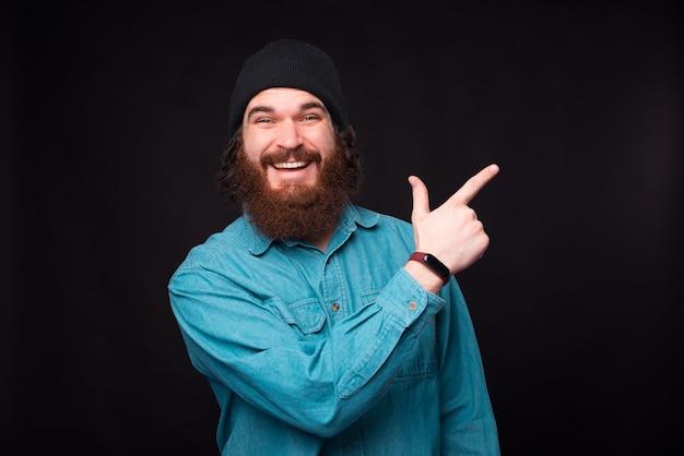 Фотография молодого бородатого хипстера, смеющегося в камеру и указывающего пальцем на свободное место на черной стене