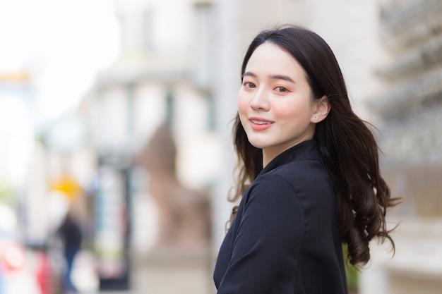 黒いローブを着た美しい長髪のアジアの美しい少女が、屋外の街を歩いて外を眺めながら幸せそうに笑っている写真。