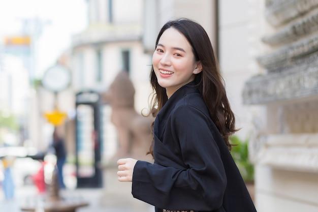 Фотография красивой длинноволосой азиатской красивой женщины в черном халате, счастливо улыбающейся идущей