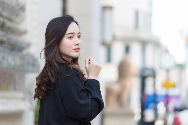 Фотография красивой длинноволосой азиатской красивой женщины в черном халате, идущей и смотрящей наружу