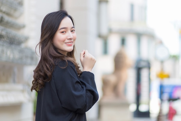 Фотография красивой длинноволосой азиатской леди в черном халате, идущей и смотрящей наружу