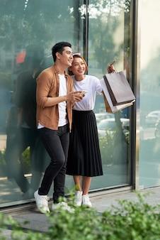 市内でスマートフォンを使って買い物をしているカップルの写真