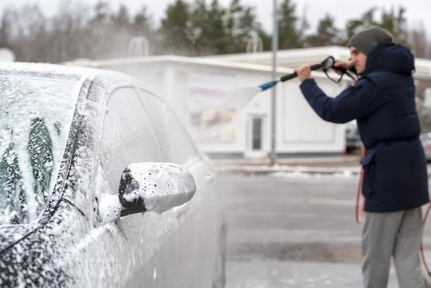 Фотография мужчины, моющего машину под высоким напором воды на улице в холодное время года.