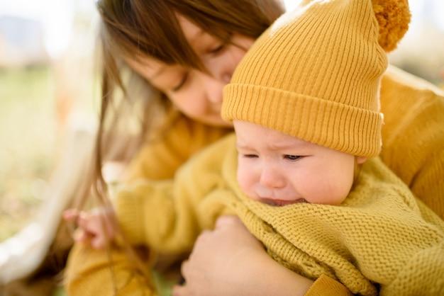 Изображение мамы, утешающей и обнимающей ее девочку в парке
