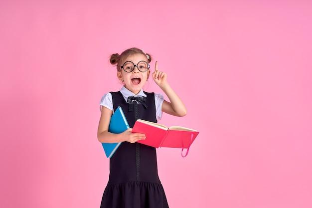 Фотография школьницы с учебником, эмоционально угадывающего, указывая на что-то над изолированным розовым пространством