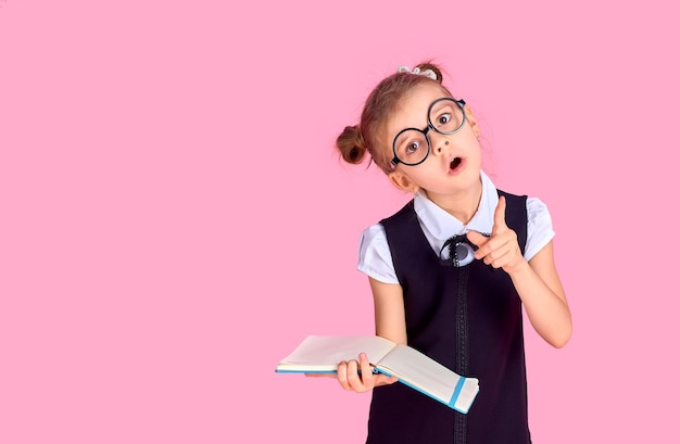 Фотография школьницы с учебником, эмоционально указывающей на что-то над изолированным розовым пространством