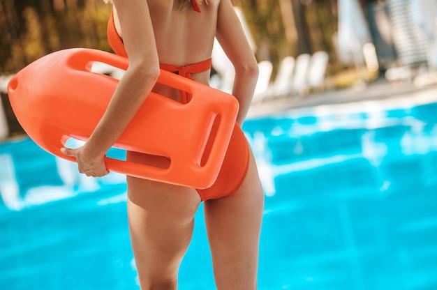 Фотография женщины в красном купальнике у бассейна