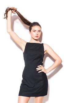 白い背景の上にポーズをとって黒いドレスを着た若い美しい女性の写真