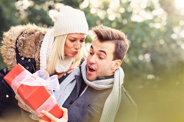 公園でプレゼントを持っている若いカップルの写真