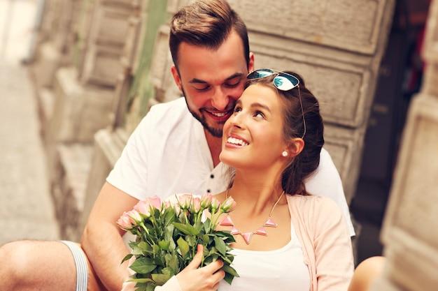 Фотография молодой романтической пары с цветами в городе