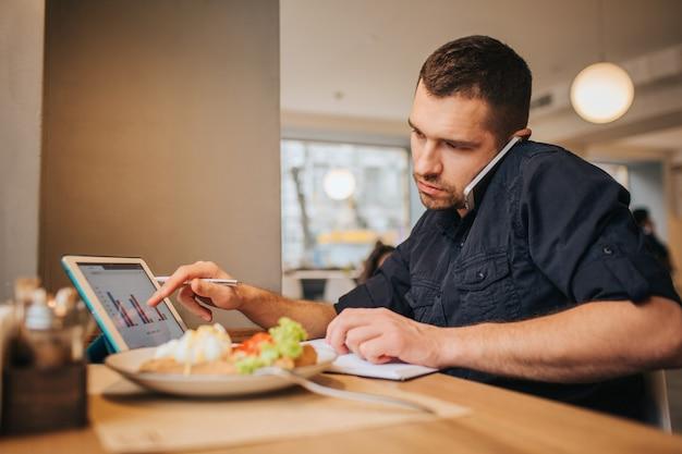カフェで食事をするビジネスマンの写真。彼は今働いています。 guyは電話で話し、タブレットの画面にグラフィックを指しています。テーブルの上に食事のプレートがあります。