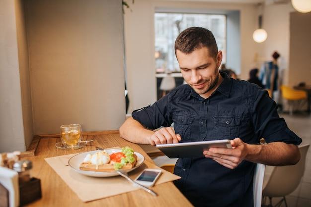 テーブルに座って働くビジネスマンの写真。彼はタブレットを使用しています。テーブルの上に美味しい食べ物と飲み物のプレートがあります。また、プレートの近くに電話があります。