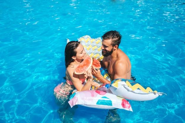 Изображение пары плавая в бассейне и полагаясь к надувному матрасу. они смотрят друг на друга. также у пары есть кусочки арбуза в руках. они едят это.