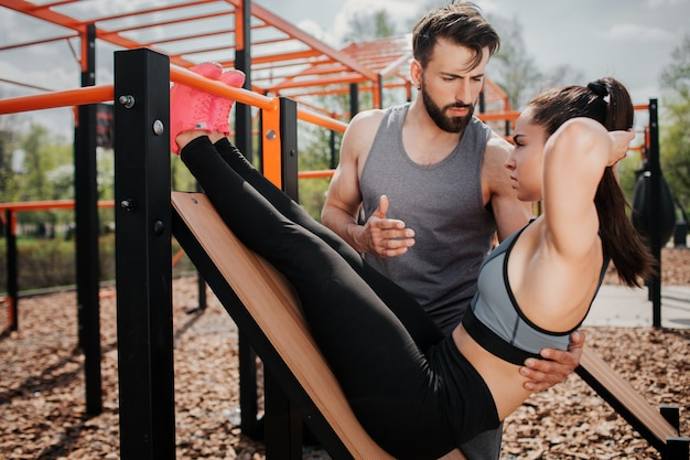Фотография девушки делает упражнения на пресс на спортивной скамейке. упражнение очень интенсивное. парень советует ей