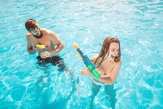 スイミングプールで男を攻撃している女の子の写真。彼は水鉄砲から撃っています。女の子は自分を守り悲鳴をあげようとしています。