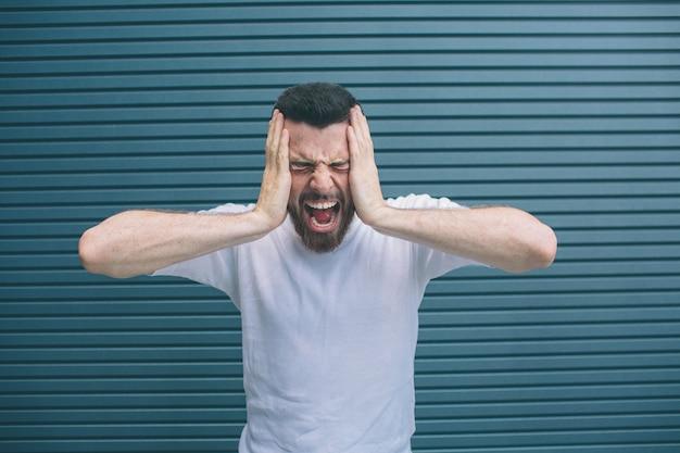 Картина парень страдает от головной боли. он держит руки на лице и кричит. он чувствует себя ужасно. изолированные на полосатый