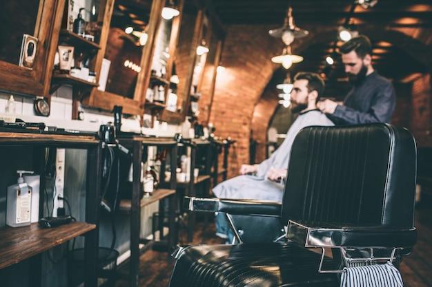Изображение парикмахера, стоящего на спине у его клиента и накрывающего его плечи.