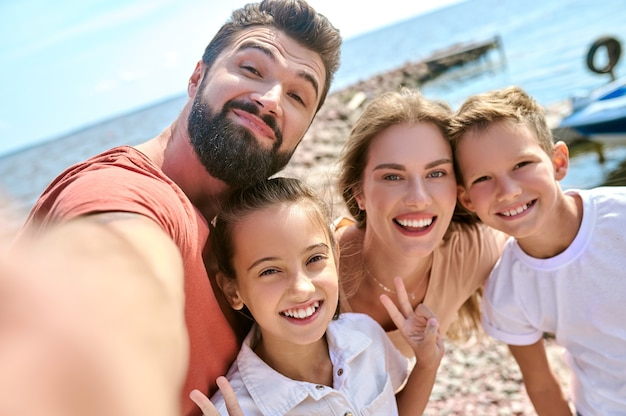 Фотография счастливой улыбающейся семьи, развлекающейся на пляже
