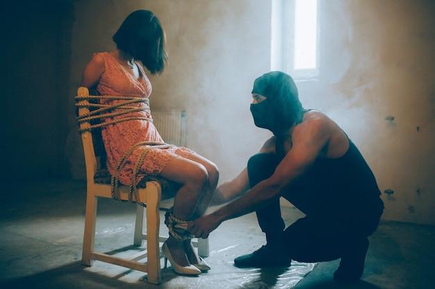 Фотография похищенной девушки, сидящей на стуле. она связана веревками. ее руки и ноги связаны. ее похититель сидит рядом с ней и смотрит на нее. парень держится руками за ноги девушки.
