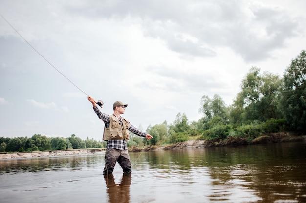 フライロッドを右手で持っている男性の写真。彼は浅瀬に立って、まっすぐ見ています。彼は餌を入れたスプーンの一部を投げて魚を捕まえる準備ができています。
