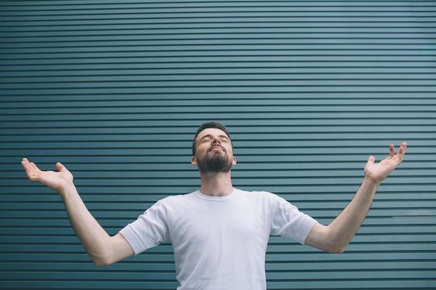 Изображение человека в белой рубашке стоя и держа руки по разные стороны. он смотрит вверх. парень держит глаза закрытыми. он молится изолированные на полосатый