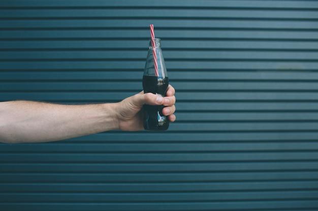 Изображение мужской руки, держащей бутылочку кока-колы с соломой в нем. изолированные на полосатый