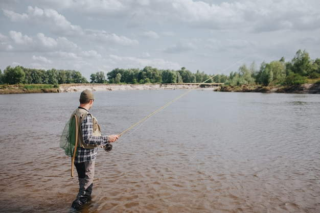 水に立って釣りをしている男の写真。彼は手で回転し、水を見ています。ガイは背中に漁網を持っています。彼は落ち着いていて集中しています。