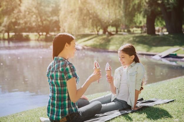 Изображение мамы и дочери сидя на одеяле около озера. они держат в руках мороженое. девушка смотрит на мороженое. женщина смотрит на ребенка.