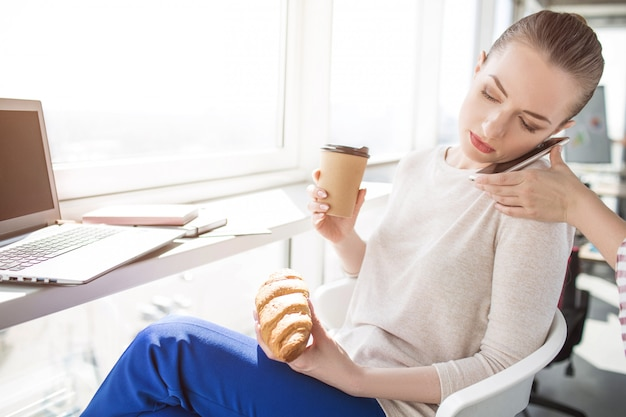 전화 통화하는 심각한 비즈니스 여자의 그림. 누군가 그녀가 전화를 올바른 위치에 놓도록 도와줍니다. 그녀는 손에 음식과 음료를 마시기 때문에 혼자 전화를 할 수 없습니다.