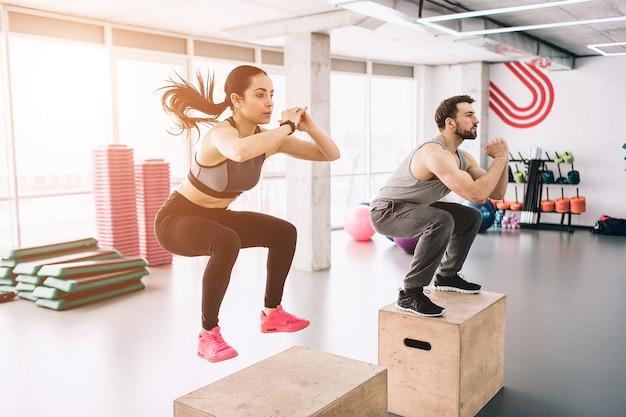 날씬하고 잘 생긴 젊은 남녀가 플랫폼에서 점프하는 사진. 힘든 운동이지만 성실하고 성공적으로 해내고 있습니다.