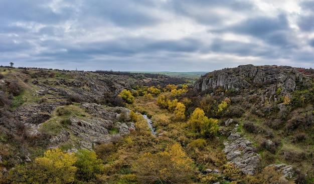 В актовском каньоне течет живописный ручей в окружении осенних деревьев и больших каменных валунов.
