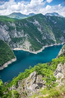 高い山の頂上から美しいターコイズブルーの湖を見ることができます。
