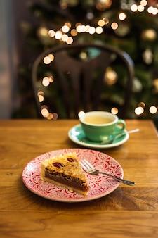 皿にピーカンパイとコーヒー1杯、背景にボケライト、セレクティブフォーカス