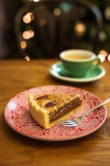 皿の上のピーカンパイと一杯のコーヒー、背景のボケライト
