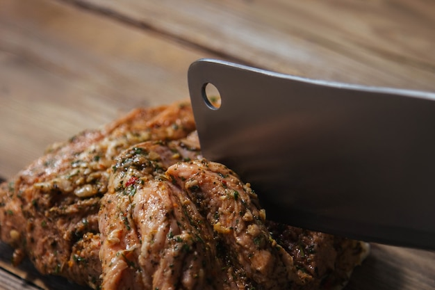 향신료와 함께 그릴에 구운 고기 조각이 나무 표면 클로즈업에 놓여 있습니다.