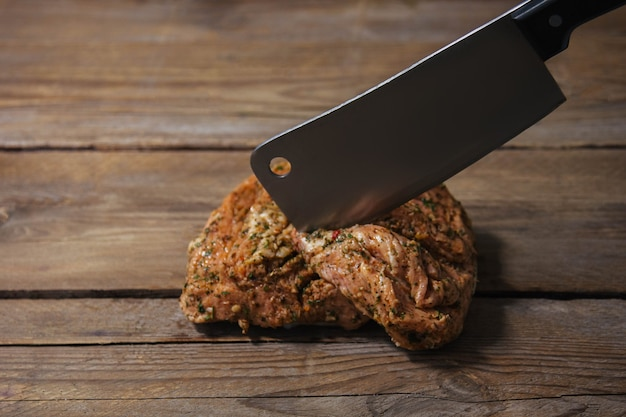 Кусок запеченного мяса на гриле со специями лежит на деревянной поверхности крупным планом