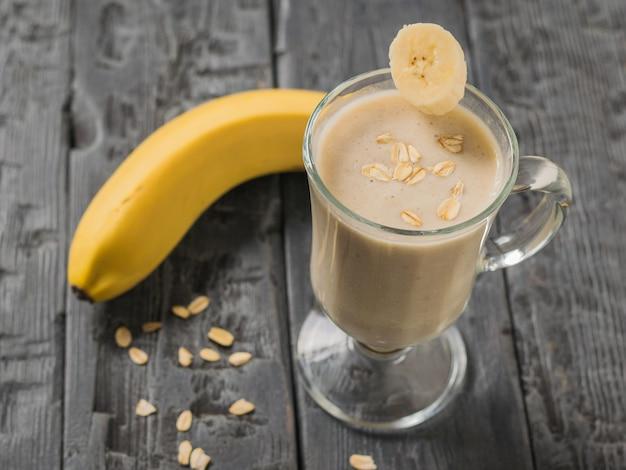 Кусок банана в стакане с банановым смузи. вегетарианский смузи. спортивное питание.