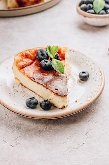 Положить кусок баскского обожженного чизкейка, весь торт на заднем плане. тарта де кесо.