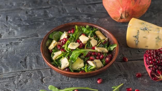 블루 몰드 치즈와 arugula 및 석류 샐러드 조각 소박한 테이블에. 다이어트 채식 샐러드.
