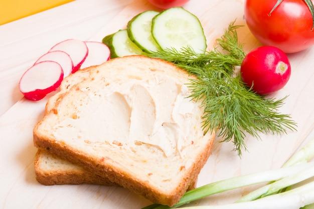 木製のテーブルの上にフムス、野菜、ディルを広げたパン