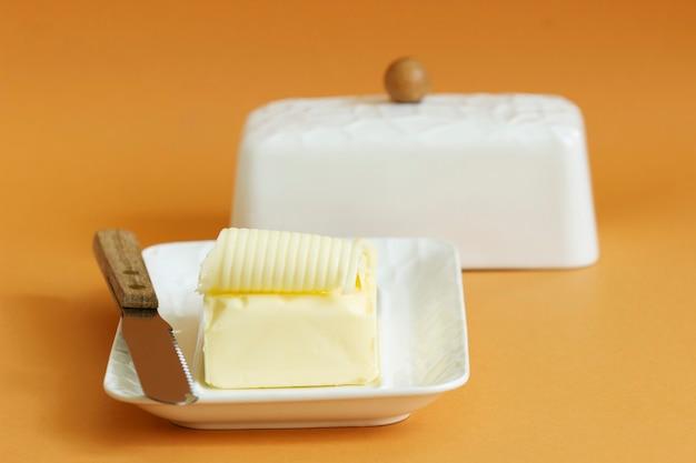 Кусок масла в масленке и нож на цветном фоне. выборочный фокус.