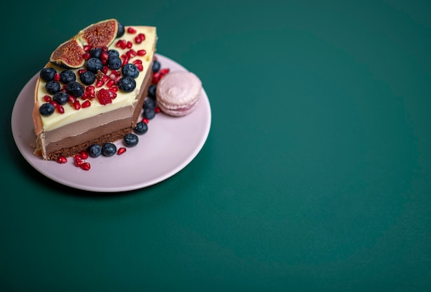 ピンクのプレートに新鮮なベリーとマカロンを添えたケーキ、ダークグリーンにお茶のマグカップ