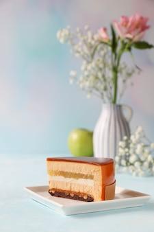 Кусок торта на тарелке с цветами в вазе и яблоком на