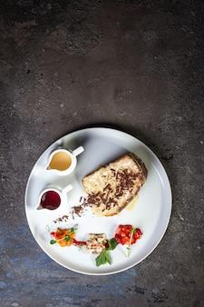 하얀 접시 윗면에 연유를 넣은 케이크 한 조각