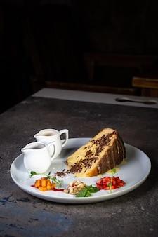 흰 접시에 연유를 넣은 케이크 한 조각