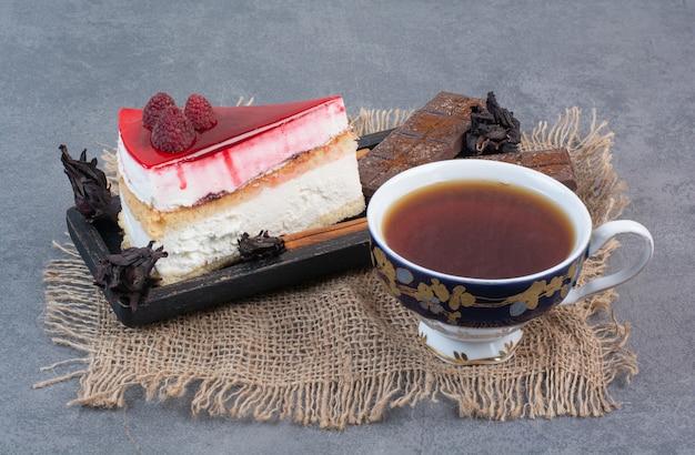 Кусок торта с чашкой ароматного кофе на сером столе.