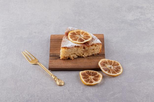 포크와 말린 레몬 조각을 곁들인 케이크 한 조각이 돌 테이블에 놓여 있습니다.