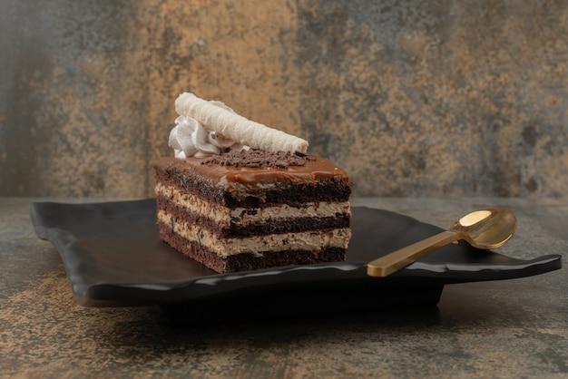 暗いプレートに金色のスプーンでケーキ