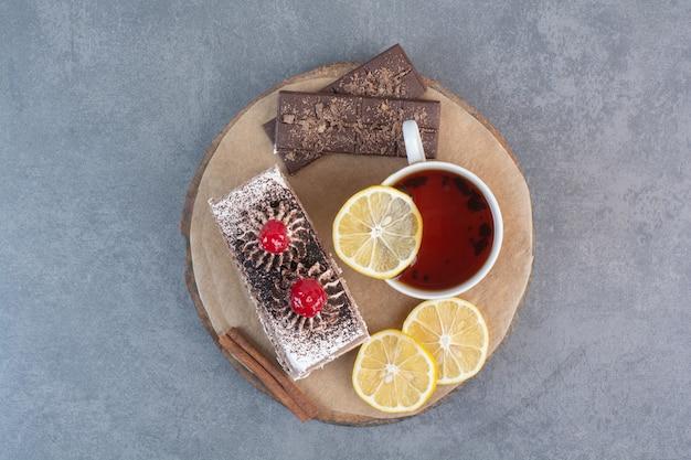 Кусок торта с нарезанным лимоном и палочкой корицы на деревянной доске.