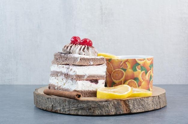 Кусок торта с нарезанным лимоном и палочкой корицы на деревянной доске